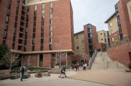 Students walk near the on-campus student housing buildings.