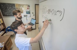 Jongwoo Choi and faculty Kevin McGown work out math problems on a white board.