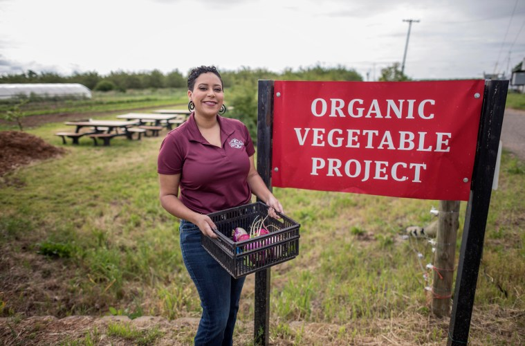 "Kaeli McCarther stands next to a sign that reads ""Organic Vegetable Project"" while holding a crate of vegetables."