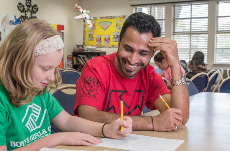 A student works teaches a girl at the Boys and Girls Club how to write in Arabic as part of a volunteer program.