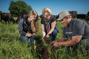Cindy Daley and two students crouch in a field of grass holding piles of soil in their hands.