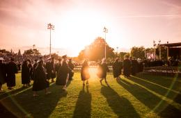 New;ly graduated students return to their seats after receiving their diplomas in front of a sunset backdrop.