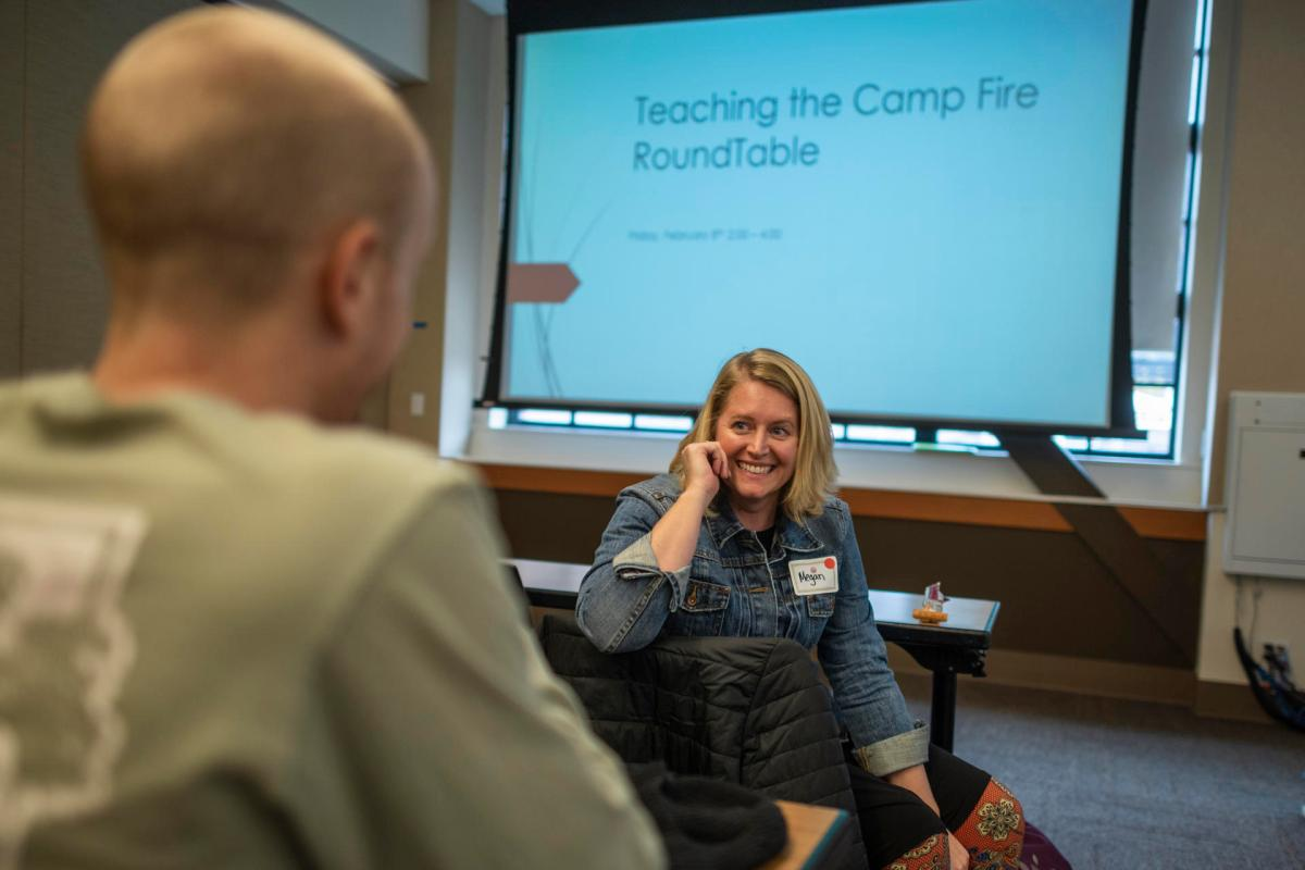 As she waits to speak in front of educators about teaching the Camp Fire on campus, she smiles and shares a lighthearted moment with a colleague.
