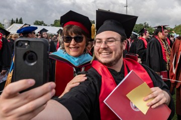 President Hutchinson and Joseph Arballo pose for a selfie at graduation, both in their regalia.