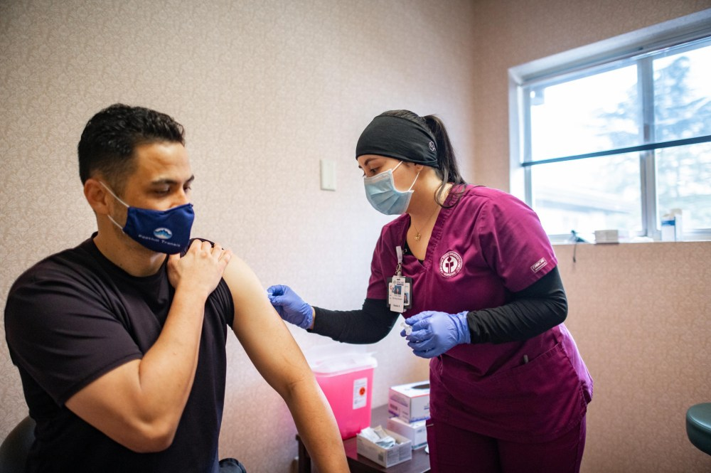 A nursing student prepares the arm of a recipient of a vaccination.