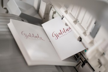 The cover of the gratitude journal prints out of the printer.
