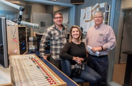 Three NSPR employees sit in a news studio among radio equipment.