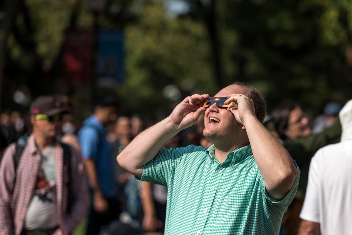 Nick Nelson smiles as he wears protective glasses and looks at a solar eclipse among a large crowd at Chico State.