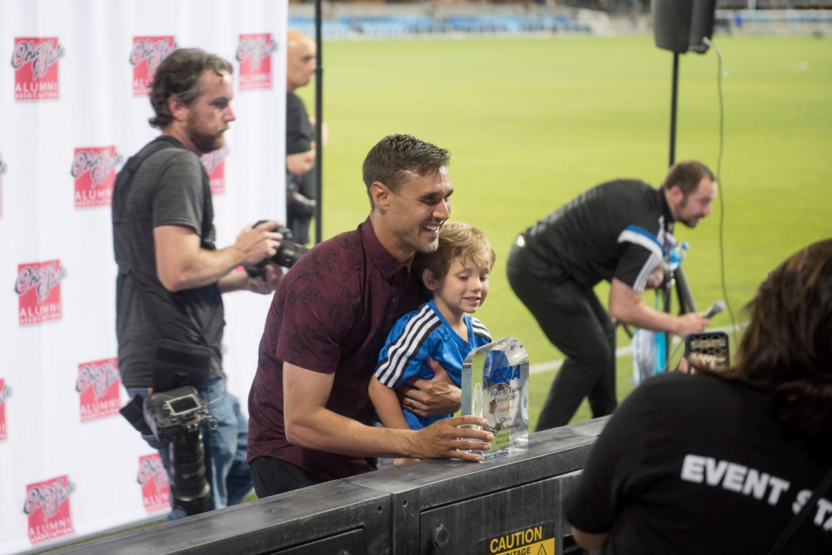 Chris Wondolowski takes time to pose for photos with a young fan.