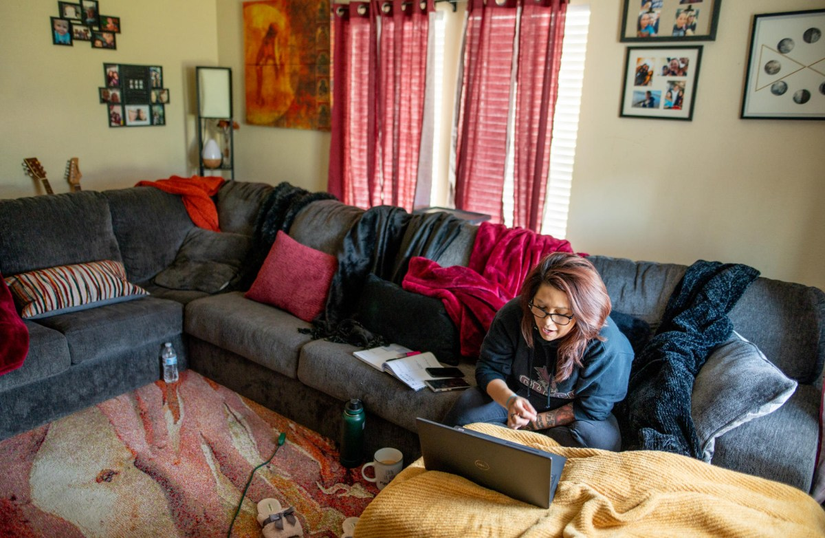 Irene Echavarria sits on her couch as she talks to fellow students via her laptop during a class.