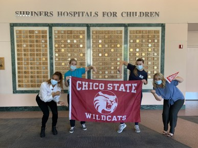 Four masked women pose with a Chico Sate Wildcats flag at Shriners Hospital