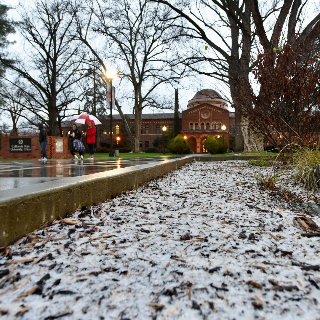 A heavy layer of hail gives the appearance of a snowy scene in front of the Kendall Hall walkway
