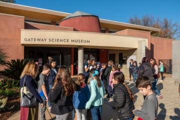 Elementary school students and teachers eagerly await the opening of the Gateway Science Museum for their field trip.