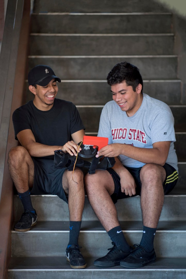 Two students sit on a stair, smiling and together holding the robotic knee brace prototype they built.