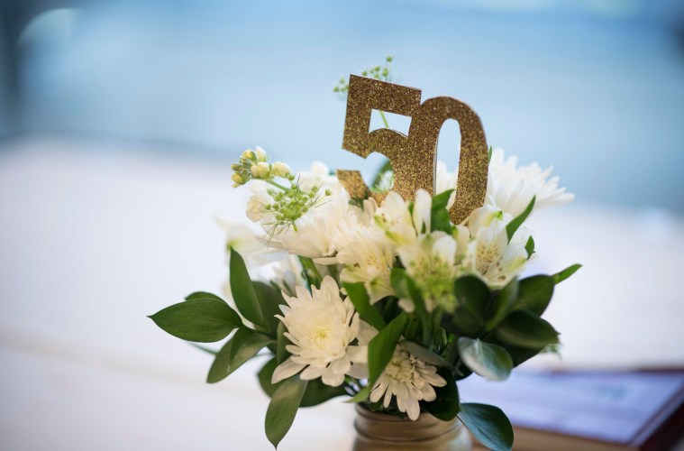 A flower arrangement with the number 50 sits on a table.
