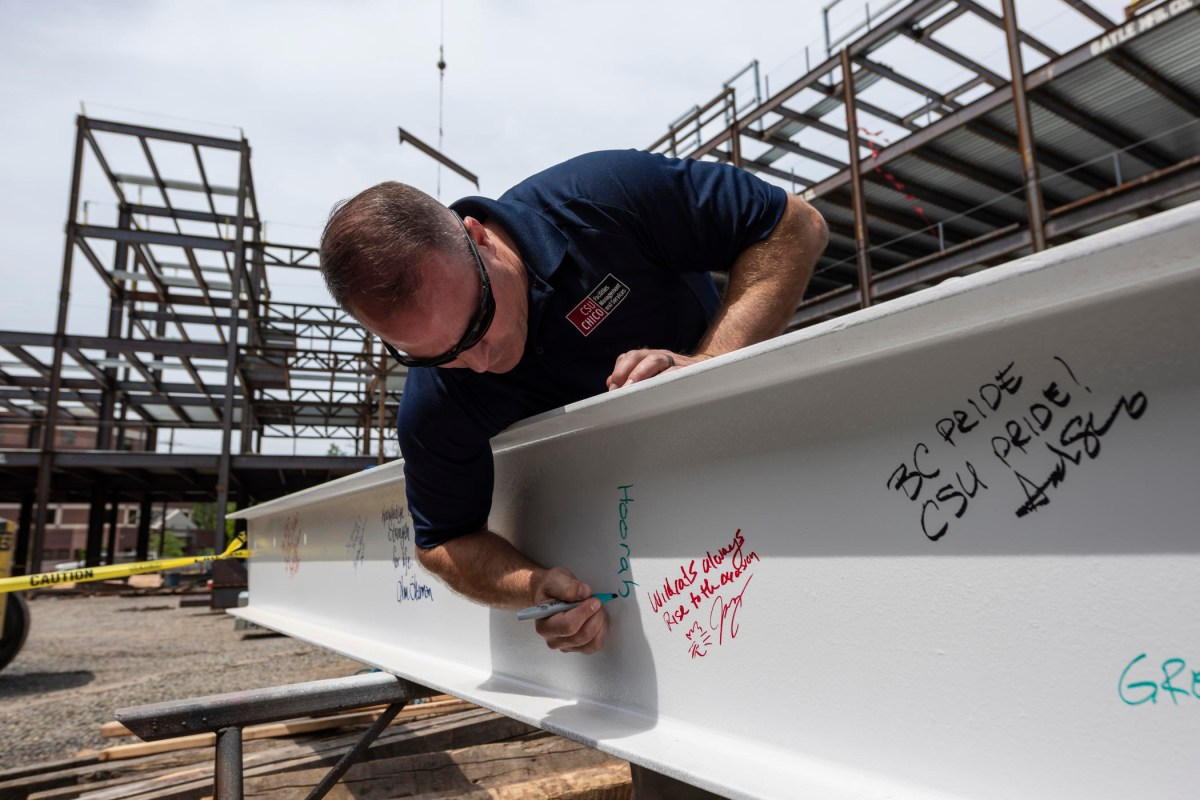 "Mike Guzzi signs ""Hoorah"" on a steel beam in the new physical sciences building."