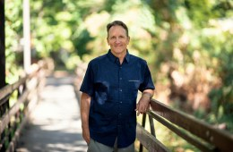 Portrait of Al Schademan standing on a campus bridge.