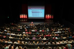 A matrix of the Strategic Plan lights up on a screen on the Harlen Adams Theatre stage to a crowd of hundreds in the audience.