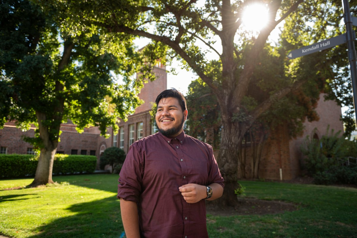 Gustavo Martir smiles in front of Trinity Hall with the sun shining through the trees in the background