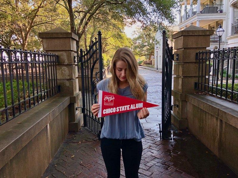 Savannah Anderson looks down at a Chico State pennant she holds in her hands in a South Carolina neighborhood.
