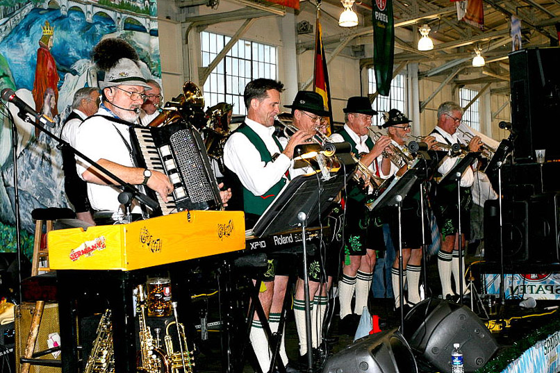 A group of musicians play a variety of instruments on stage while dressed in traditional German clothing.