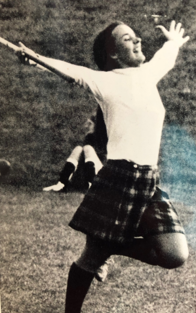 President Hutchinson runs through a field, arms outstretched, wearing a plaid skirt, in this black and white photo.