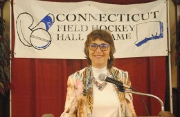 President Hutchinson stands at a podium below a Connecticut Field Hockey Hall of Fame banner.