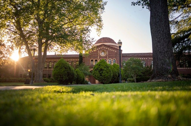 The sun sets behind a wide brick building with trees and grass in the foreground.