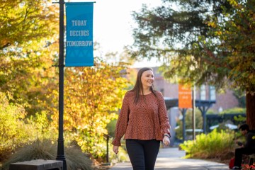 "Kelsea Kennedy walks down a path on campus near a pole banner that reads ""Today Decides Tomorrow"""