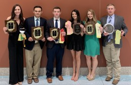 Six college students smile and hold awards.