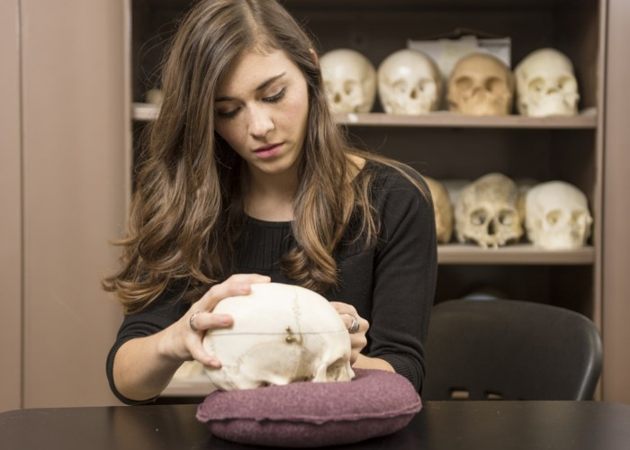 Martha Diaz holds a skull in her hands with a closet of skulls behind her.