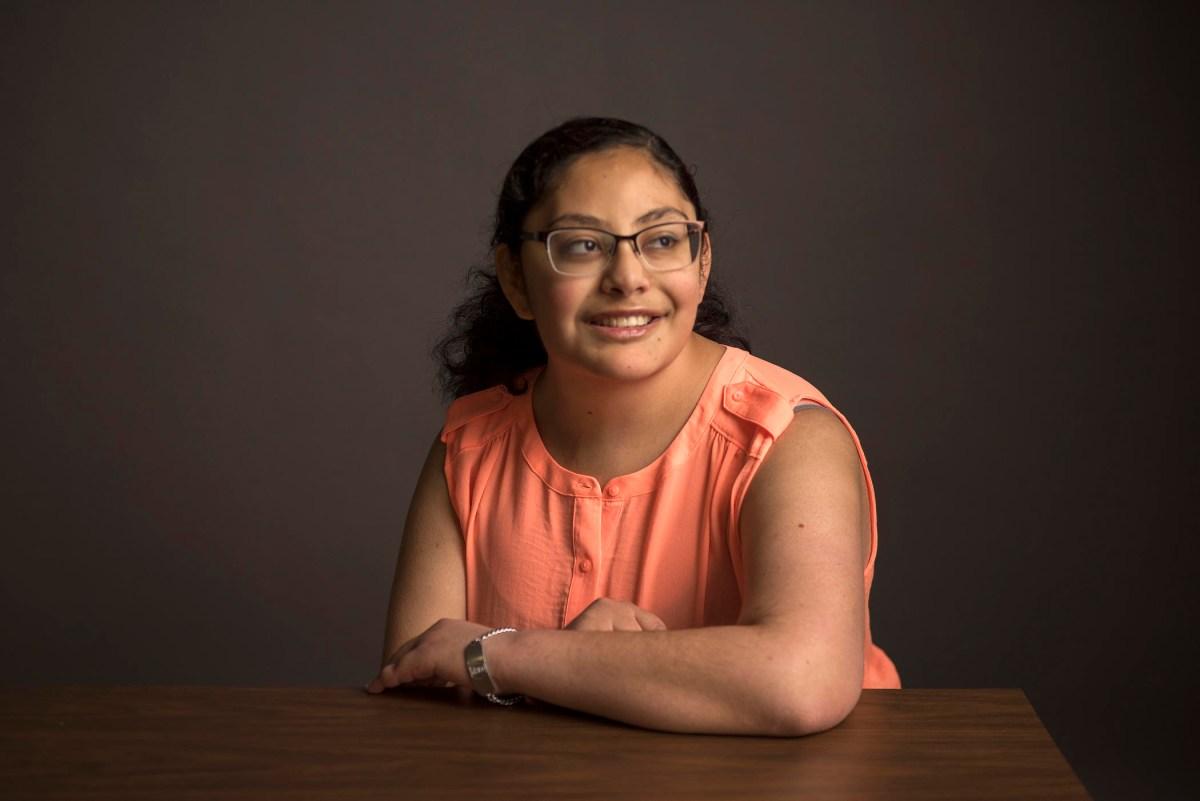 Naomi Ramirez sits at a desk for a portrait.