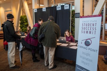 Conference attendees register at a table.