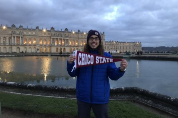 A student stands on the banks of a lake holding a Chico State banner, with a building behind him.