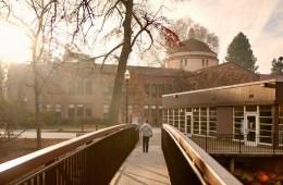 A person walks across a campus bridge, toward the rising sun.
