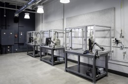 Three industrial robots are lined up inside a room.