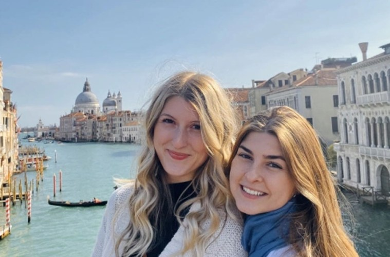 The author poses with a friend near a canal in Venice.