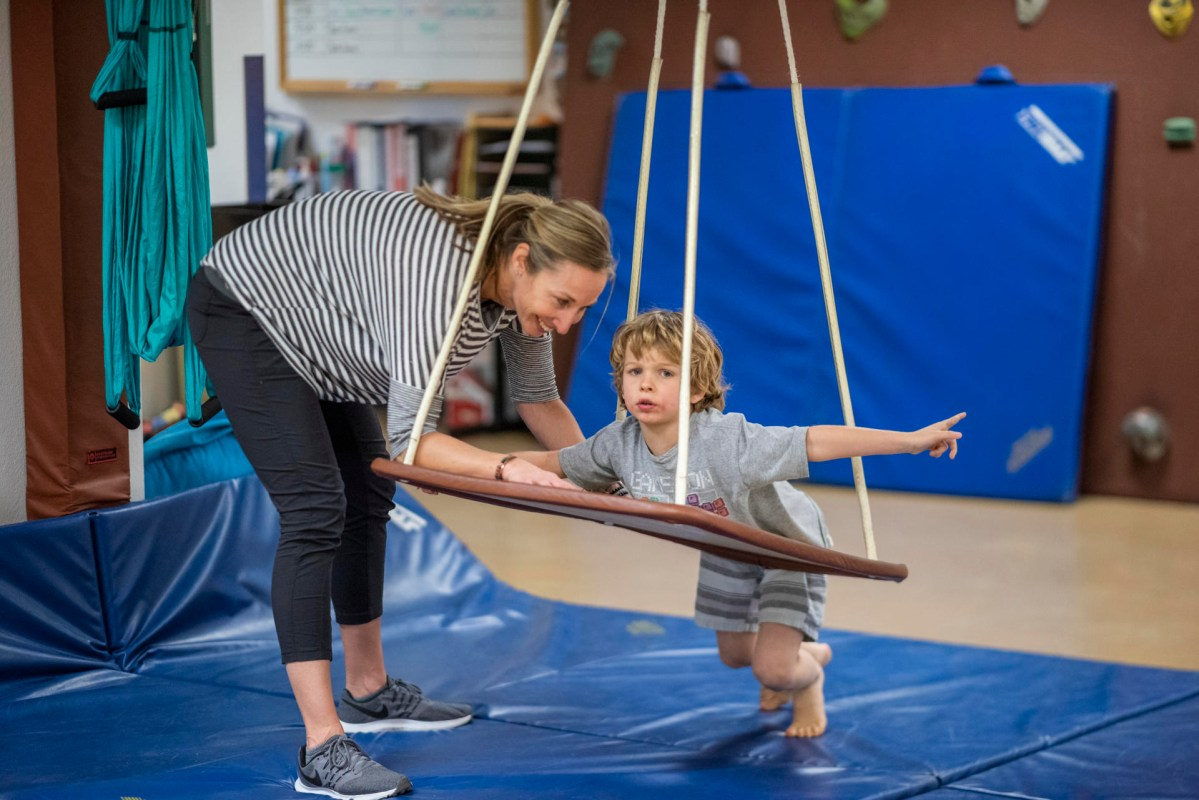 A clinician and a child work on a modified swing.