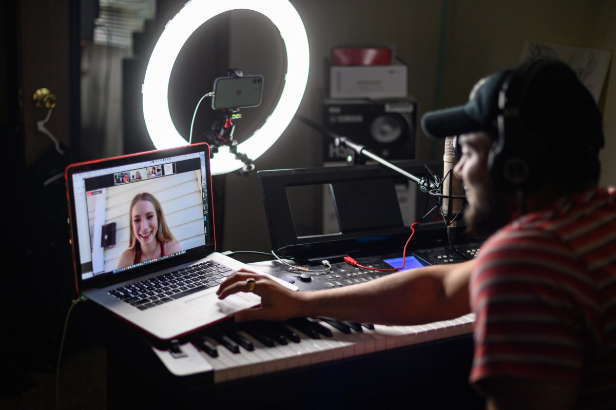 Daniel Hernandez talks to a student via zoom as he is lit up by a Halo light for audio recording.