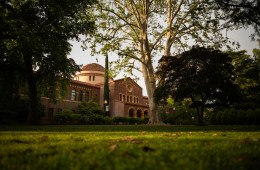 An academic building sits amongst majestic trees with a lush green lawn in front.