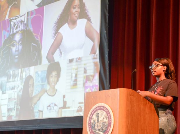 Darlasia Miller speaks from a podium with a powerpoint behind her of black women and their hair.