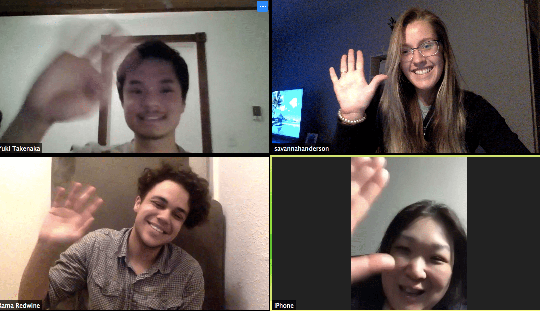 Four people wave at one another while each on their own screen on Zoom.