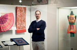 William Nitzky stands in the Valene L. Smith Museum with an exhibit behind him.