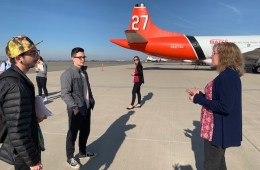 students talk with the airport manager on the tarmac of the airport with a plane in the background.