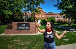 Diana Castellanos gives a virtual campus tour, holding out her self-phone while filming herself in front of the California State University, Chico monument sign.