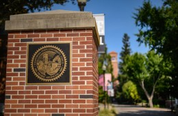 A plaque of Chico State's seal is mounted on a brick pillar, with blue skies and lush trees in the background.
