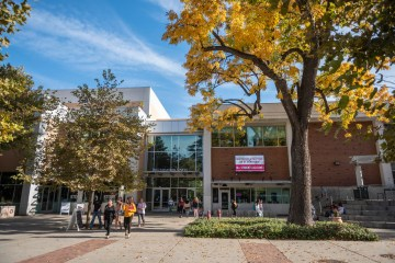 students walk out of the bell memorial union on a fall day.