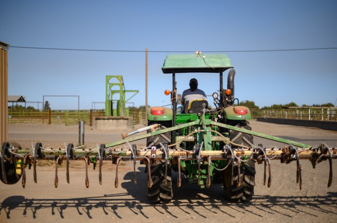 Saira Barajas drives a tractor with harrow