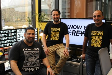 The three cofounders of Reyets pose in their office in branded tshirts.
