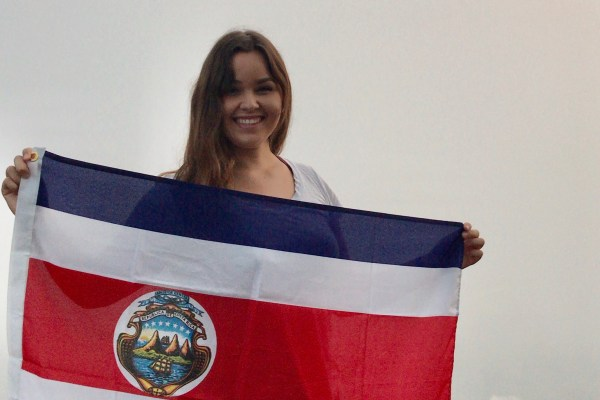 A college student smiles while holding a country's flag.